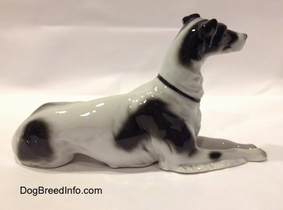 The right side of a white with black vintage TMK-1 crown mark Borzoi. The figurine is glossy. The dog has short small ears, a long neck and a thin black collar.