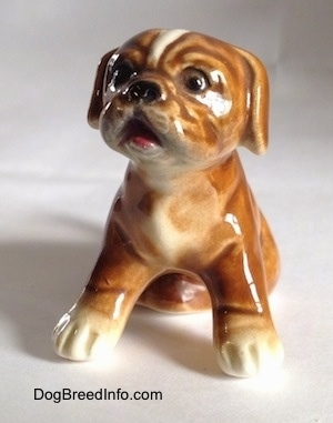 A brown with white Boxer puppy figurine that is in a sitting pose. The figurine is very glossy.