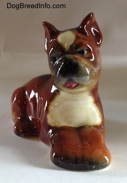 A brown with white and black Boxer puppy figurine. The figurine is very glossy.