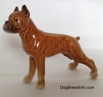 The left side of a porcelain brown Boxer dog figurine in a show stance. The figurine has a black circles for eyes.