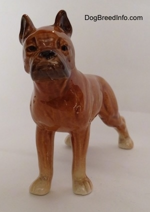 A porcelain brown Boxer dog figurine. The figurine has a detailed face.