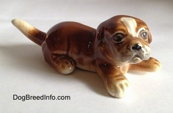The front right side of a brown with white Boxer puppy figurine. The figurine is very detailed.
