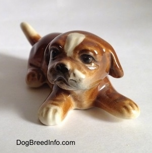 A brown with white Boxer puppy figurine. The figurine has lightly detailed paws.