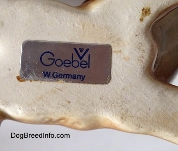 The underside of a brown with white Boxer puppy figurine. The figurine has a sticker with the Goebel W.Germany logo on it.