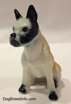 A red and white with black bone china Boxer figurine that is in a sitting pose.