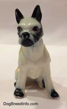 A red and white with black bone china Boxer figurine that is in a sitting pose. The figurine has black ears.