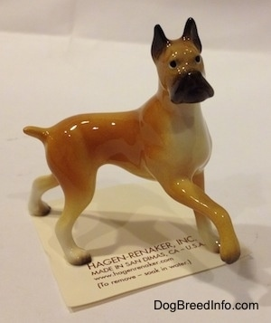 The right side of a tan with black and white Boxer mama figurine. The figurine has a detailed black muzzle.
