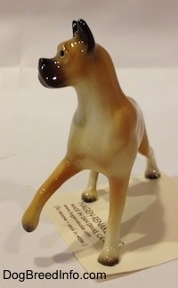 A tan with black and white Boxer mama figurine. The figurine has black circles for eyes.