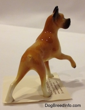 The back right side of a tan with black and white Boxer mama figurine. The tail of the figurine is indistinguishable from the body.