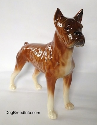 The front right side of a brown with black and white Boxer dog figurine. The eyes of the figurine are hard to differentiate from the face.