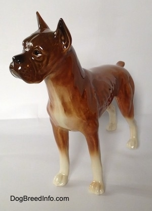 The front left side of a brown Boxer dog figurine. The figurine is very glossy.