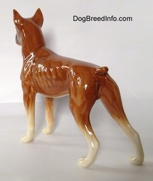 The back left side of a brown Boxer dog figurine. The figurine has detailed paws.