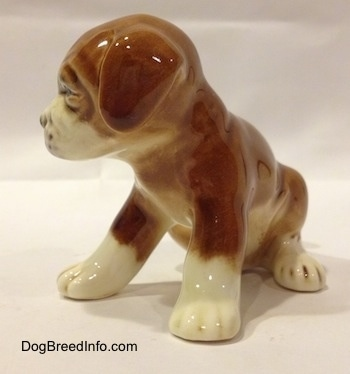 The front left side of a brown with white Boxer puppy figurine. The figurine has fine paw details.