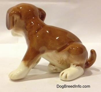 The left side of a brown with white Boxer puppy figurine. The tail of the figurine is arched up and touching the ground.