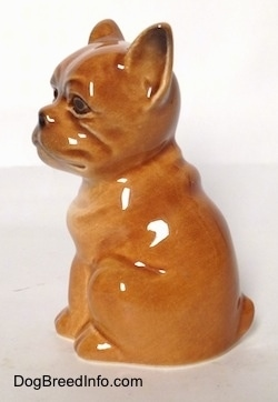 The left side of a brown Boxer puppy figurine. The figurine is very glossy.