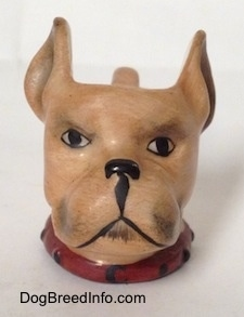 A stein cup that is in the shape of head of a Boxer dog. The eyes and the mouth of the stein are painted on.