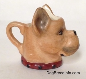 The right side of a stein cup that is in the shape of head of a Boxer dog. The stein has a collar painted on it.