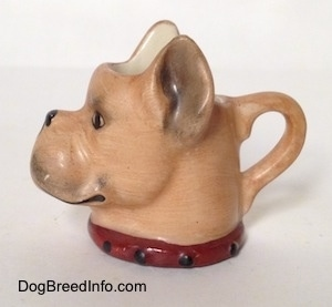 The left side of a stein cup that is in the shape of head of a Boxer dog. The stein has detailed ears.