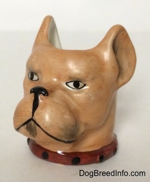 The front left side of a Stein Cup of a Boxer dogs head. The cup has a red with black collar on.
