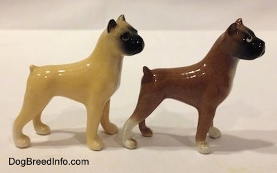 The right side of two color variations of a miniature Boxer dog standing figurine. Both figurines have black muzzles.