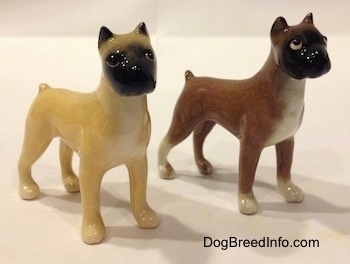 The front right side of two color variations of a miniature Boxer dog standing figurine. Both figurines have detailed eyes.