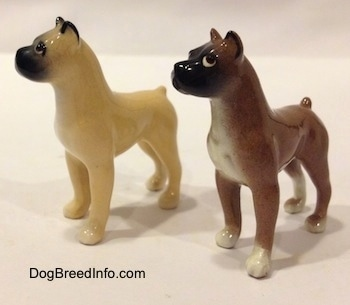 The front left side of two color variations of a miniature Boxer dog standing figurine. Both figurines have short tails.