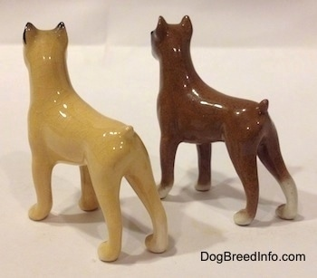 The back left side of two color variations of a miniature Boxer dog standing figurine. The figurines are glossy.