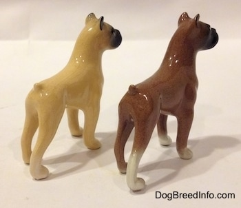 The back right side of two color variations of a miniature Boxer dog standing figurine. The ear tips of both figurines are black.