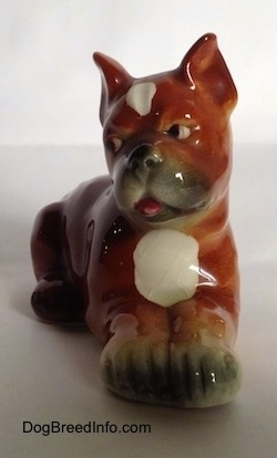 A brown with white and black Boxer puppy figurine. The pink tongue of the figurine is sticking out.