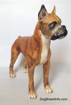 The front right side of a brown with black and white Boxer figurine with a matte finish. The figurine has very detailed paws.