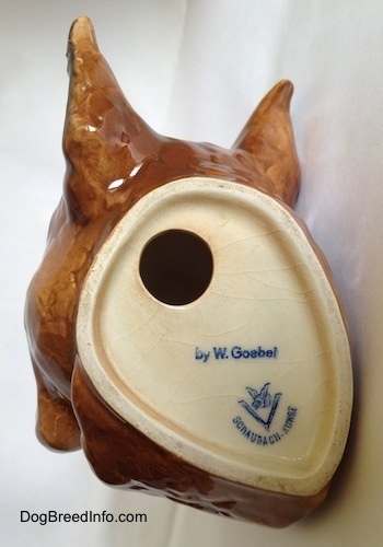 The underside of a fawn Boxer head wall mount. The logo of Goebel W. Germany is on the underside and there is a hole above it.