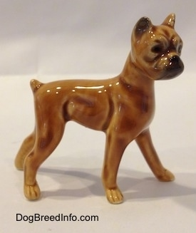 The right side of a brown with black mini Boxer dog porcelain figurine. The figurine has great shaping details.