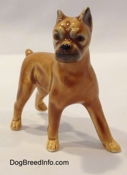 The front left side of a brown with black mini Boxer dog porcelain figurine. The figurine has black circles for eyes.