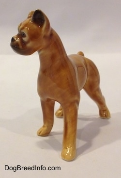 The front right side of a brown with black mini Boxer dog porcelain figurine. The figurine does not have fine paw details.