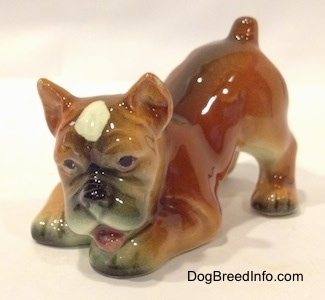 The front left side of a brown, black and white Boxer puppy figurine in a play bow pose. The figurines mouth is open.