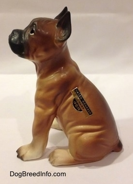 The left side of a brown with black and white Boxer puppy figurine. The figurine is highly detailed.