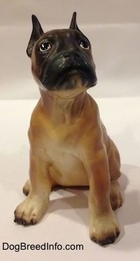 A brown with black and white Boxer puppy figurine. The figurine has a detailed face.