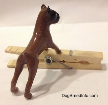 The back right side of a brown with black Boxer dog figurine that is placed on top of a clothespin. The figurine lacks fine details.