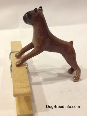 The left side of a brown with black Boxer dog figurine that is placed on top of a clothespin. The figurine has a short tail.