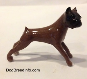 The left side of a brown with black Boxer dog figurine.