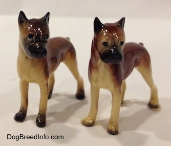 The front left side of two different color variations of the miniature Boxer Mama figurine. The figurines both have black circles for eyes.