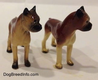 Two different color variations of the miniature Boxer Mama figurine.