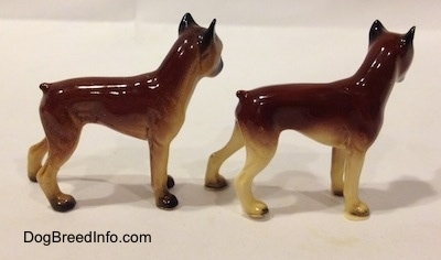 The right side of two different color variations of the miniature Boxer Mama figurine. The figurines both have short tails.