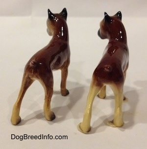 The back right side of two different color variations of the miniature Boxer mama figurine. The figurines have black ears.