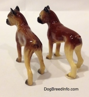 The back left side of two different color variations of the miniature Boxer mama figurine. The figurines both have great paw details.