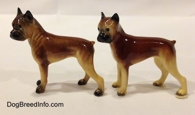 The left side of two different color variations of the miniature Boxer Mama figurine. The figurines are glossy.
