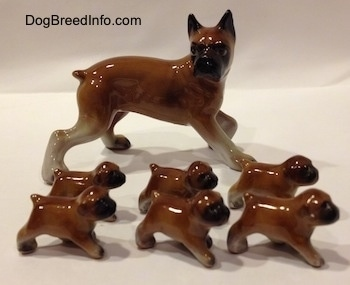 The right side of a brown with white and black Boxer mom with 6 puppies figurines. All of the figurines have black muzzles.