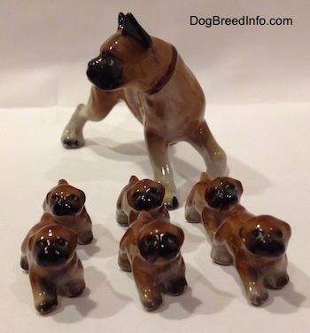 A brown with white and black Boxer mom with 6 puppies figurines. All the figurines have black circles for eyes.