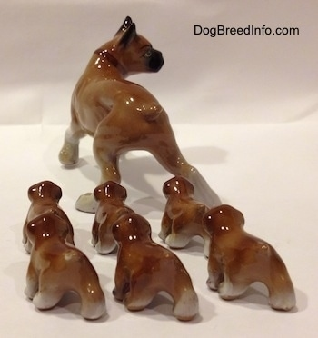 The back side of a brown with white and black Boxer mom with 6 puppies figurines. It is hard to differentiate the tails from the bodys of the figurines.