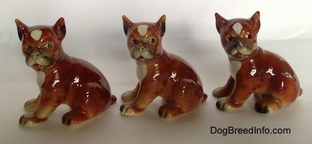 The left side of three brown with white and black Boxer puppy figurines that are slightly different.